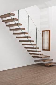 Scala a sbalzo con gradini in legno e ringhiera in vetro